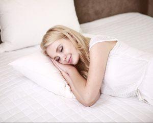 Frau liegt im Bett mit Schafstörungen